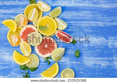 Set of sliced citrus fruits. Different sliced juicy citrus fruits on rustic wooden table - stock photo