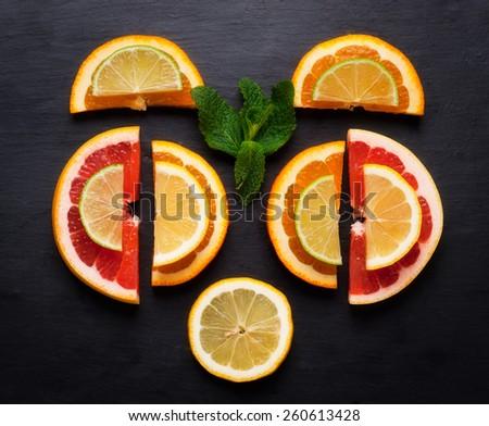 Set of sliced citrus fruits lemon, lime, orange, grapefruit over black texture.Top view - stock photo