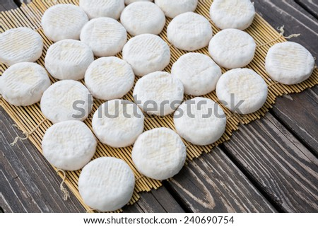 Set of small heads of goat cheese crottin  lying on wooden boards