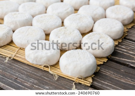Set of small heads of goat cheese crottin  lying on wooden boards - stock photo