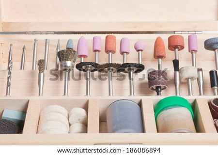 Set of specialised drill bits with grinding wheels, polishing and buffing heads and wire brushes for use in various handicrafts neatly stored in a wooden tray - stock photo