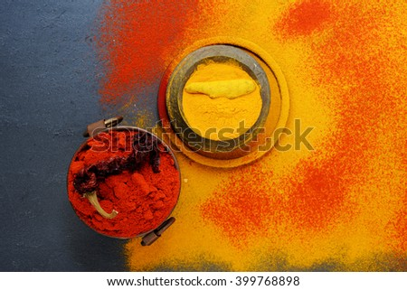 Set of spices pepper and turmeric, in vintage metal cups over yellow turmeric powder. Top view. Food or spicy cooking concept, Healthy eating Background. - stock photo