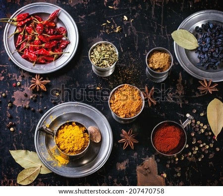 Set of spices pepper, turmeric, anise, coriander in vintage metal cups over old wooden table. Top view. - stock photo