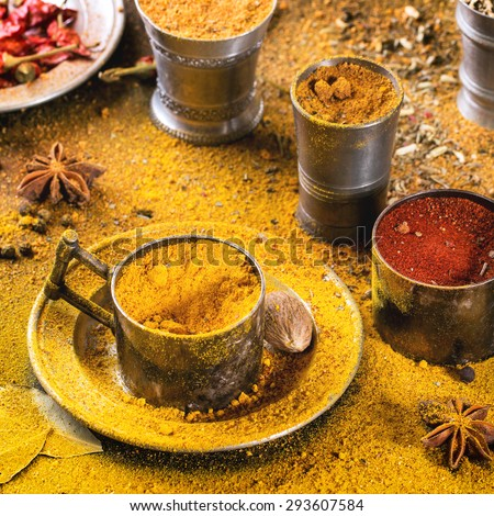 Set of spices pepper, turmeric, anise, coriander in vintage metal cups over yellow curry powder. Square image with selective focus. - stock photo