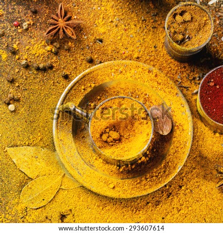 Set of spices pepper, turmeric, anise, coriander in vintage metal cups over yellow curry powder. Top view. Square image. - stock photo