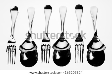 Set of stainless steel fork and spoon reflection on white background - stock photo