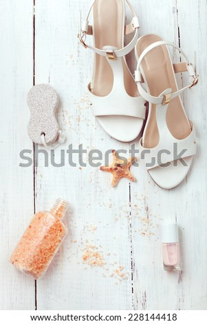 Set of summer women's accessories - sandals, sea salt, pumice stone and nail polish, on wooden floor. White collection. - stock photo