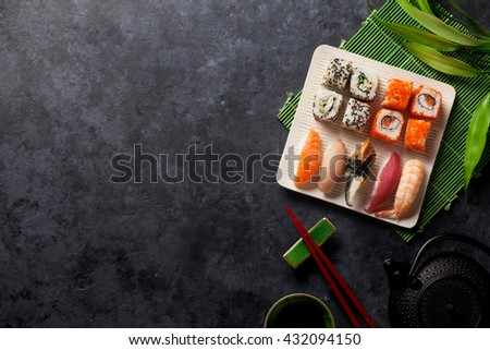 Set of sushi, maki and green tea on stone table. Top view with copy space - stock photo
