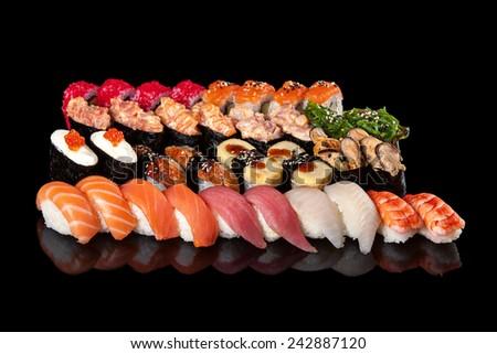 set of sushi rolls and sashimi on a black background - stock photo