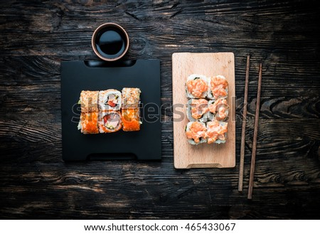 set of sushi rolls with salmon topping on wooden board