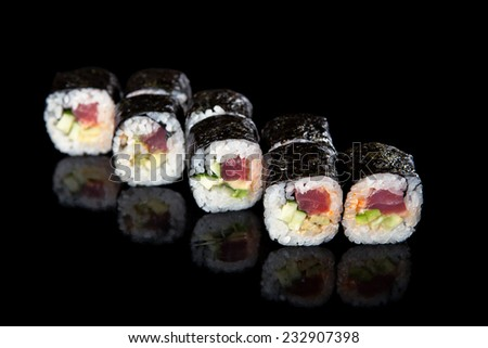 set of sushi rolls with tuna on a black background - stock photo