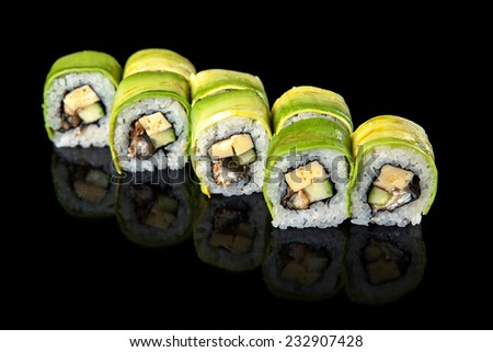 set of sushi rolls wrapped in avocado on a black background - stock photo