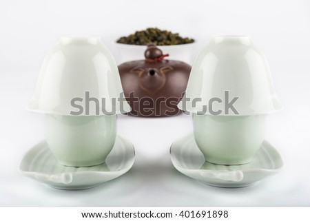 Set of tea Yin and Yang cups, teapot and bowl with tea. Isolated - stock photo