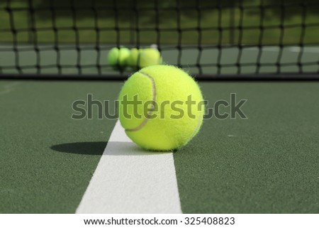 Set of tennis balls on a green tennis court