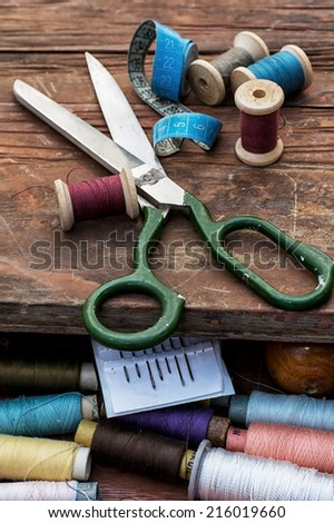 set of threads of different types,colors and lengths on wooden background - stock photo