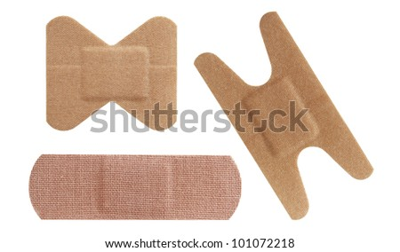 Set of three bandaids or bandages in various shapes over white. - stock photo