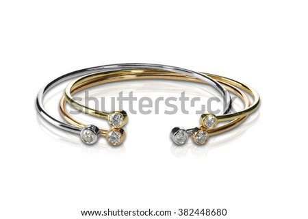 Set of three colored gold and diamond bracelets stacked isolated on white with a reflection