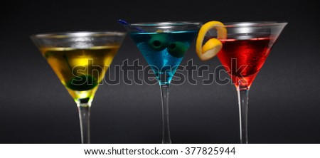 Set of three colorful martini cocktails against black in a studio. - stock photo