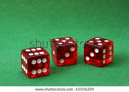 set of three dice on green background