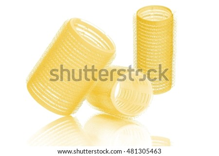 Set of three different sizes yellow hair curlers, isolated on white background, with reflection
