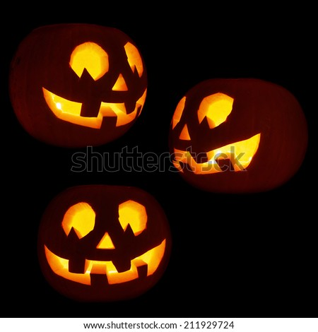 Set of three glowing Jack-o'-lanterns pumpkins isolated over black background - stock photo