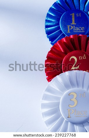 Set of three winners rosettes and ribbons in red, white and blue with gold lettering for 1st, 2nd, and 3rd place on white with copyspace - stock photo