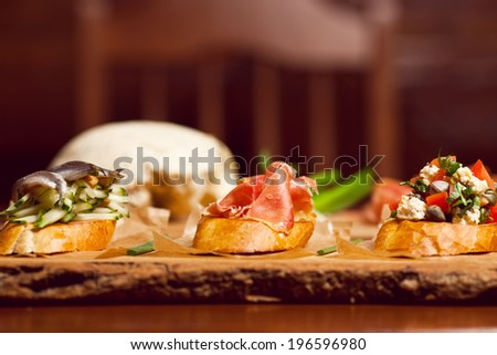 Set of toasts with fresh and pickling cucumber, goat cheese, italian parma ham, anchovies and tomatoes, served with pieces of parchment on wooden board. Close up - stock photo