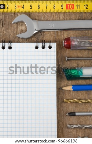 set of tools and notebook on wood background texture - stock photo