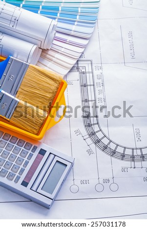 set of tools calculator paintbrushes in paintcan color palette rolled blueprints - stock photo