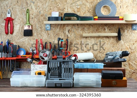Set of tools in workshop on plywood background - stock photo