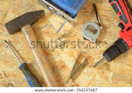 Set of tools - jigsaw, drill, screws, hammer, screwdriver and construction meter placed on OSB board