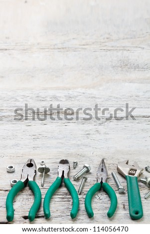 Set of tools on painted wood background - stock photo