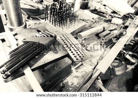 Set of tools over a wood panel on black and white - stock photo