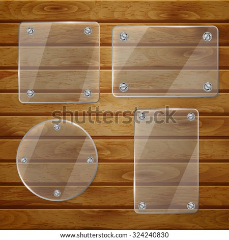 Set of transparent glass plates of different shapes, bolted to wooden planks - stock photo