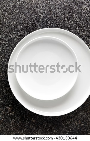 Set of two Porcelain Plates on a black Marble table. Empty space - stock photo