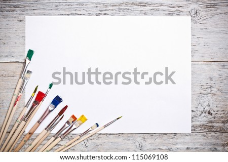 Set of used paint bruches with paper on wood background - stock photo