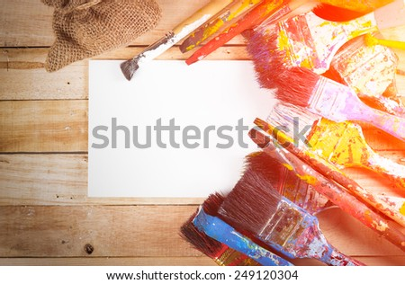 Set of used paint bruches with paper on wood background,vintage color toned image - stock photo