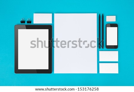 Set of variety blank office objects organized for company presentation or branding identity with blank modern devices. Isolated on blue paper background. - stock photo