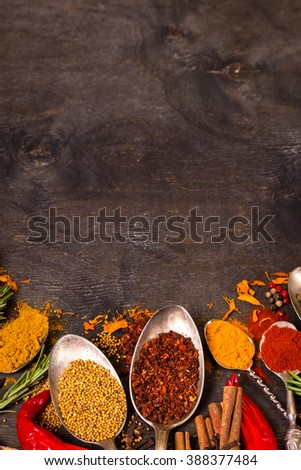 Set of various aromatic colorful spices in old vintage spoons and herbs on a dark wooden background. Space for text. Food frame. Ingredients for cooking. Top view - stock photo