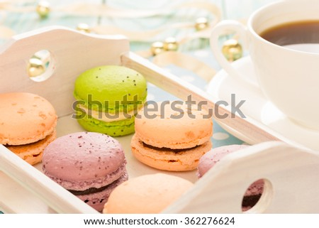 Set of various colored macaroons on wooden plate