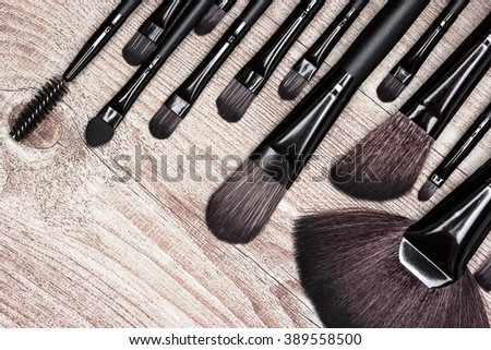 Set of various natural bristle makeup brushes: for applying foundation, blush, eyeshadow, fan brush and others. Professional tools of make-up artist on shabby wooden surface - stock photo