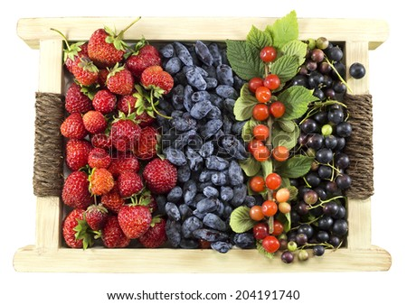Set of various summer berries in wooden box on white - stock photo