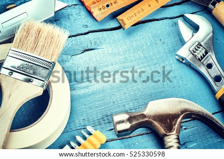 Set of various tools on blue wooden background. Construction and renovation concept with copy space