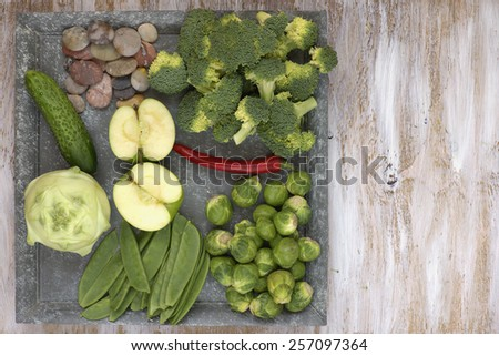 Set of vegetables on white painted plate and wooden background: kohlrabi, cucumber, apple, pepper, brussels sprouts, pea pods, broccoli. - stock photo