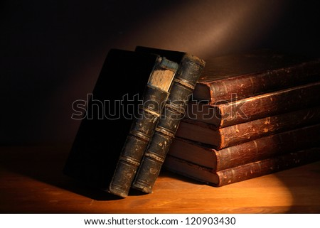 Set of very old books on dark background - stock photo