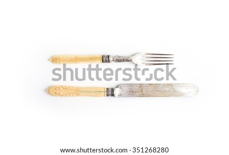 Set of vintage dinnerware. Knife and fork with bone handles on a white background. Top view - stock photo