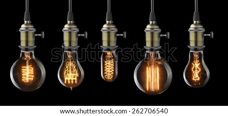 Set of vintage glowing light bulbs on black - stock photo