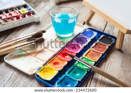 Set of watercolor paints, art brushes, glass of water and easel with painting on old wooden table. - stock photo