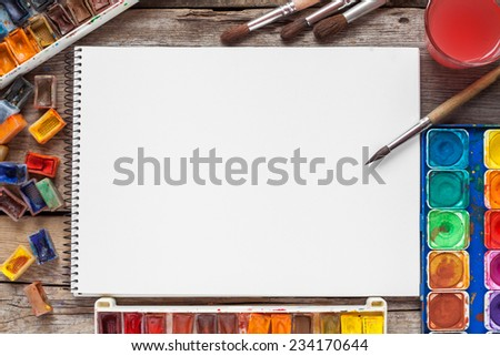 Set of watercolor paints,  brushes for painting and blank white paper sheet of sketchbook on vintage wooden background. Top view. - stock photo