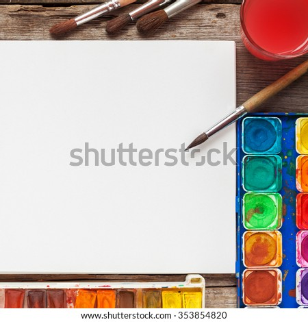 Set of watercolor paints, brushes for painting and blank white paper sheet of sketchbook. Top view. - stock photo